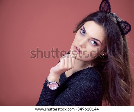 A close up portrait of a beautiful brunette girl with green eyes and black cat ears wearing a dark gray dress and glamorous watch with stones. Isolated. Pale pink background. - stock photo