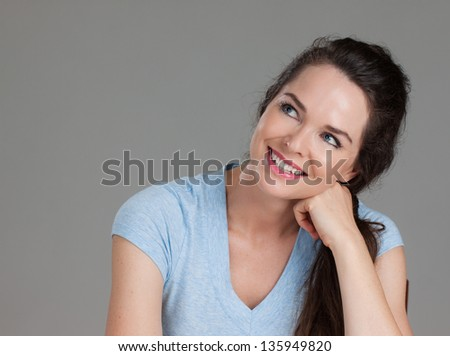 A close-up portrait of a beautiful happy smiling woman looking up at copy-space.