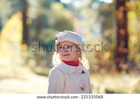 A close up portrait of a cute little girl in a white coat and elegant hat walking in a park on a sunny autumn day