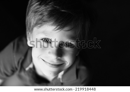 A close up portrait of a handsome smiling little boy, black-and-white photo  - stock photo