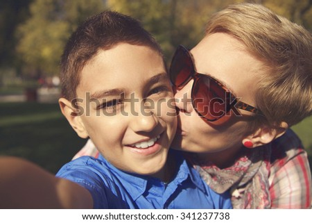 A close up portrait of a mother and her son making selfie in the park. - stock photo