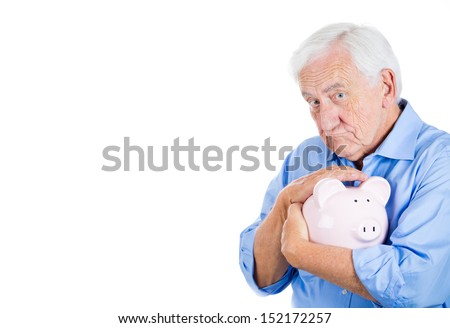 A close-up portrait of a retired old man with grey hair, holding a piggy bank, looking very serious and possessive of his savings, isolated on a white background . Smart financial decisions.