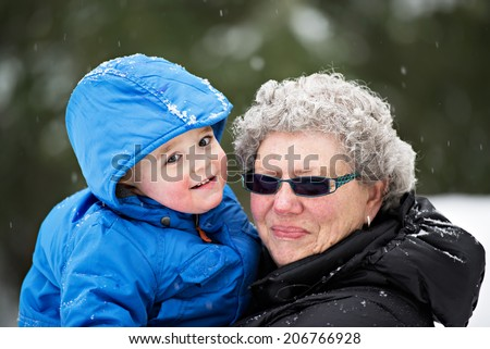 A close up portrait of a smiling grandmother holding her happy grandson outside in the winter snow.  - stock photo