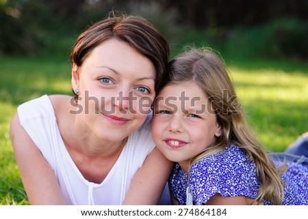 A close up portrait of a young beautiful mum and her adorable daughter outdoors in a park on a sunny summer day