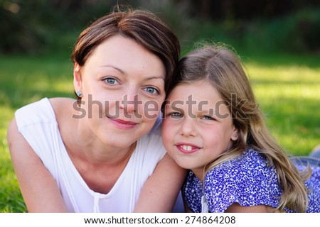 A close up portrait of a young beautiful mum and her adorable daughter outdoors in a park on a sunny summer day - stock photo