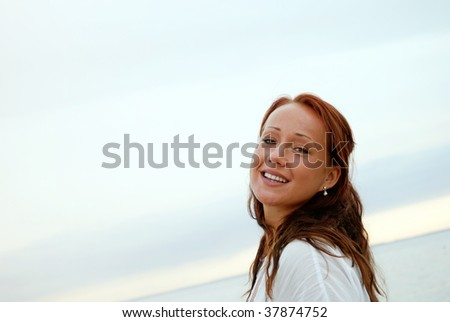 A close up portrait of a young woman smiling on a beach - stock photo