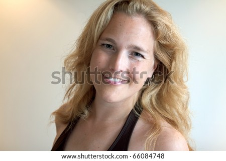 A close-up portrait of an attractive smiling adult female. - stock photo
