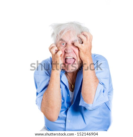 A close-up portrait of an elderly, desperate, mad, looking crazy, desperate man, going insane, isolated on a white background. Human emotions extremes. Loneliness, grief, family loss.