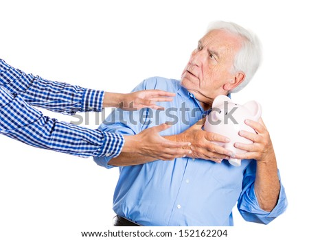 A close-up portrait of an elderly, senior man, grandfather, holding a piggy bank, looking scared, trying to protect his savings from being stolen, isolated on a white background. Financial fraud.  - stock photo