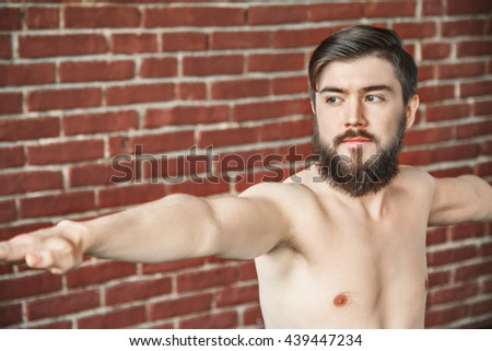 A close up portrait of man with dark hair and beard doing yoga warrior position on blue matt at wall background, copy space, portrait, virabhadrasana. - stock photo