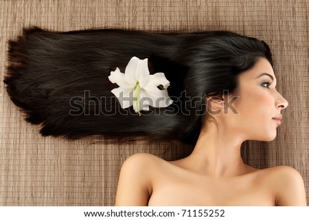 a close-up profile portrait of a young woman, laying on a spa mat. her hair is laying strait, in a horizontal direction and she har a lily flower in her hair.