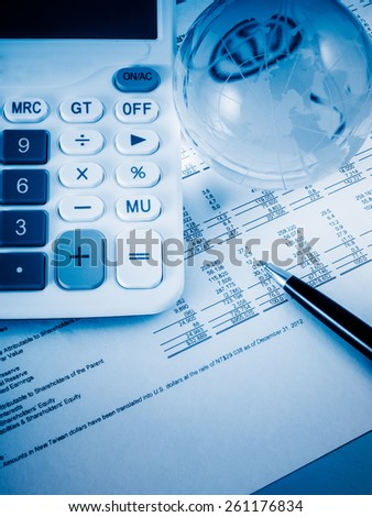 A close-up shot of a calculator.  A printed balance sheet and a pen are also visible.
