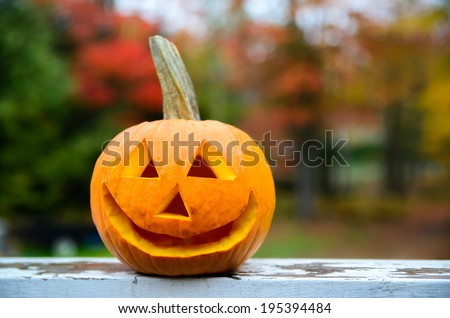 A close up shot of a happy jack-o-lantern sitting on a rail of a deck during the day with colorful autumn trees in the background.  - stock photo