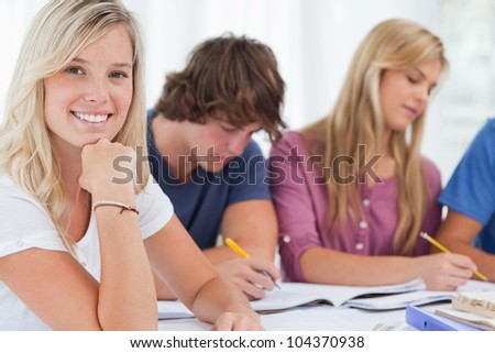 A close up shot of a smiling girl with her study friends as she looks into the camera - stock photo