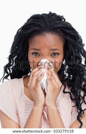 A close up shot of a woman blowing her nose in a tissue