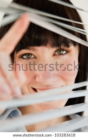 A close up shot of a woman looking through blinds straight ahead - stock photo