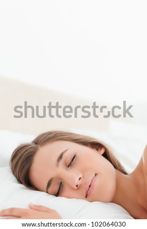 A close up shot of a woman sleeping in bed.