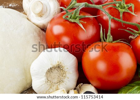 A close-up shot of different pizza ingredients, particularly on garlic and tomato - stock photo
