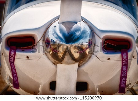 A close up shot of the hub and spinner of an airplane propeller with the ground in front of the plane reflected in the polished spinner. - stock photo