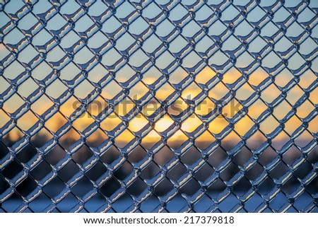 A close up shot of thick layer of ice covering a frozen metal chain link fence after an ice storm.  In the background the sun sets behind some trees.  - stock photo