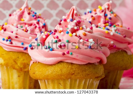 A close-up shot of three cupcakes on pink covered in sprinkles and icing. - stock photo