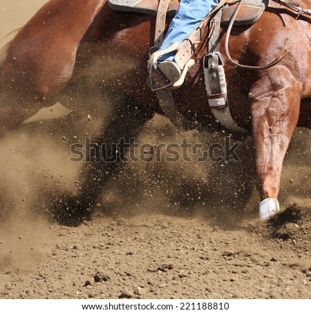A close up view of a horse sliding in the dirt. - stock photo