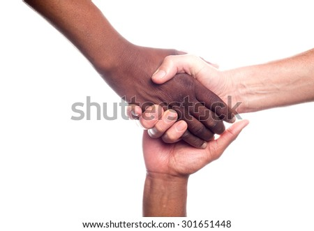 A close up view of a small group of men of mixed races holding hands in support - stock photo