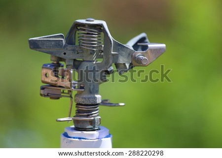 A close up view of a stainless steel sprinkler head.  - stock photo