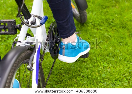 A close up view of a stylish girl riding a bicycle in the green park in summer. Wearing blue stylish clothes.