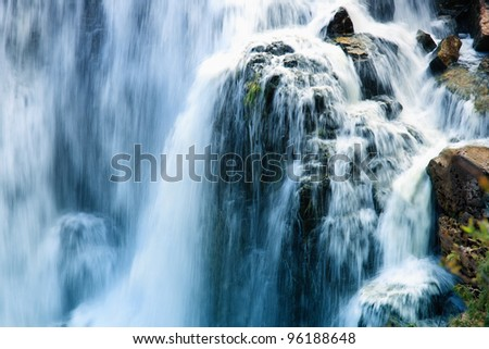 A close up view of cascading water falling over the rocks at Inglis Falls Ontario. - stock photo