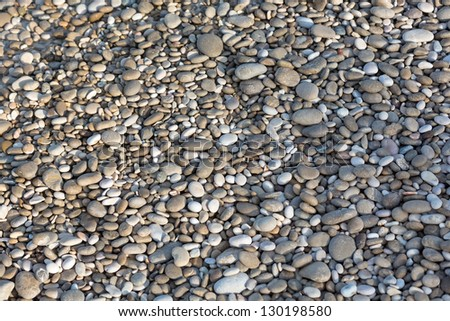 A close up view of different rounded smooth polished pebble stones on the beach - stock photo