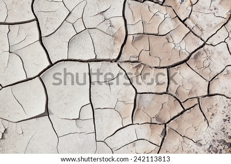 A close up view of dry cracked earth with layers pealing back and small pebbles.