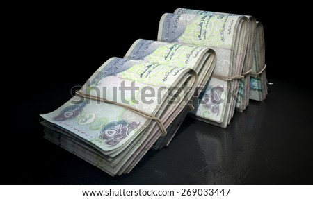 A close-up view of five wads of folded over stacks of chinese yuan banknotes each bound informally by a rubber band set out in a domino formation on an isolated dark studio background