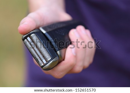 A close up view of someone holding up a razor - stock photo