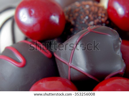 A close-up view with shallow focus of a variety of bite sized chocolates in different shapes. Some are covered with red candy coating. Some are decorated. Dark chocolate and white chocolate included. - stock photo