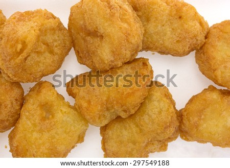 A close view of a small batch of crispy chicken nuggets on a light background. - stock photo