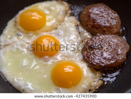 A close view of eggs and sausage frying in a skillet next to a window for natural light. - stock photo