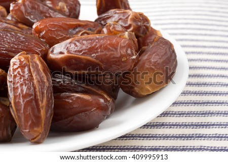 A close view of Tunisian pitted dates on a plate atop a striped table cloth.