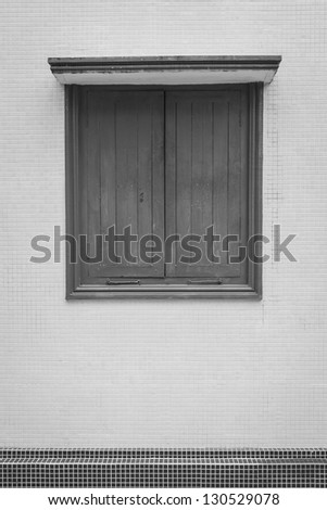A closed black window on the wall - stock photo