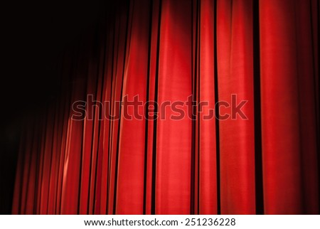 a closed red stage curtain in a small theater - stock photo