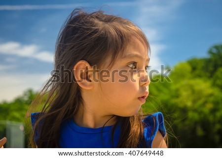 A closed up of little girl surprising at public park  with blue sky background,filtered color tone in picture. - stock photo