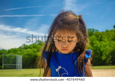 A closed up of little girl walking on sand at public park  with blue sky background,filtered color tone in picture. - stock photo