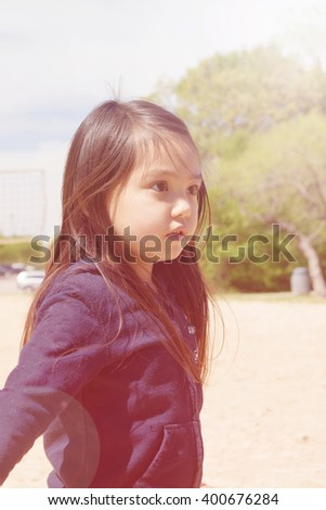 A closed up of lovely little girl playing sand at public park ,filtered color tone in picture. - stock photo