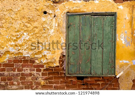 A closed wooden green window of an old brick wall