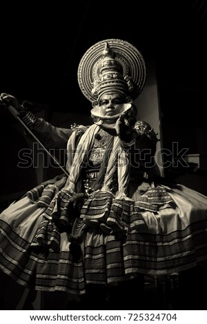 A closeup black and white portrait of a traditional Kathakali dancer performing at a local village festival in Thekkady, Kerala, India. Shot in 2012.