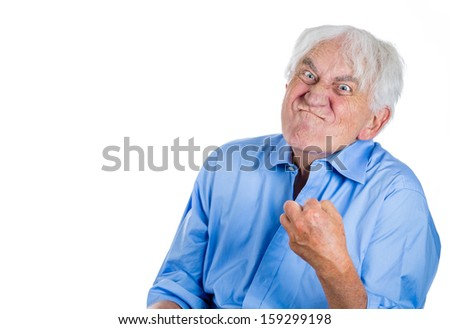 A closeup cropped portrait of an elderly, desperate, mad, looking crazy old man, going insane, showing his fist, isolated on a white background. Human emotions extremes. Loneliness, mental health - stock photo