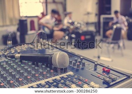 A closeup image of microphone on audio mixer's on musician blurred background on retro style - stock photo