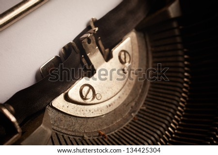 A Closeup image of the typebars and ribbon of an old style typewriter and clean paper without text (Shallow Depth of Field) - stock photo