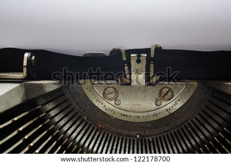 A Closeup image of the typebars and ribbon of an old style typewriter and paper (Shallow Depth of Field) - stock photo