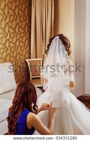 A closeup image of wedding preparations. Bridesmaid is helping put bride elegant luxury dress. - stock photo